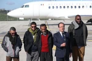 Les quatre otages d'Arlit, Marc Feret, Pierre Legrand, Daniel Larribe, Thierry Dol (de gauche à droite), le 30 octobre 2013 avec François Hollande à leur descente d'avion à l'aéroport de Villacoublay