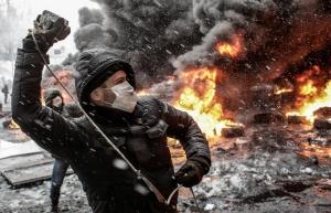 Un manifestant jetant un pavé vers les forces de l'ordre sur la place Maidan à Kiev