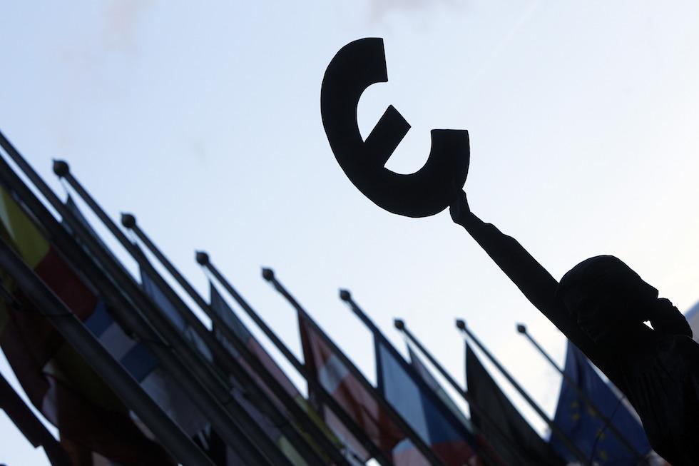 Le symbole de l'euro tenu par une statue devant le bâtiment du Parlement européen à Bruxelles - décembre 2011 © Xinhua / Allpix Press