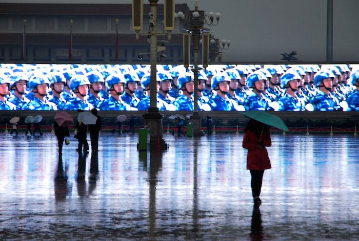 Des touristes marchent sous la pluie le long d'un grand panneau électronique sur la place Tian'anmen à Beijing, capitale chinoise, le 10 novembre 2012. Fin © Xinhua / Allpix Press - Photo : Li Gang
