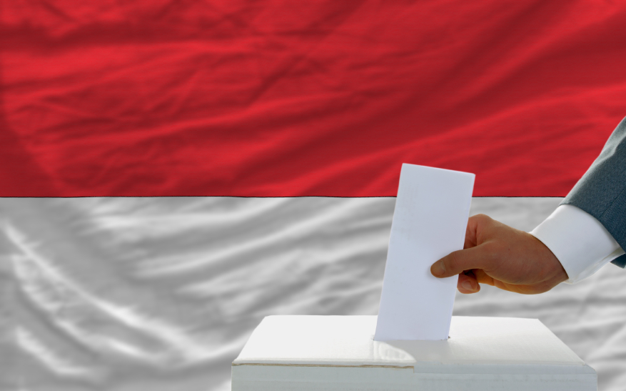 man voting on elections in indonesia in front of flag