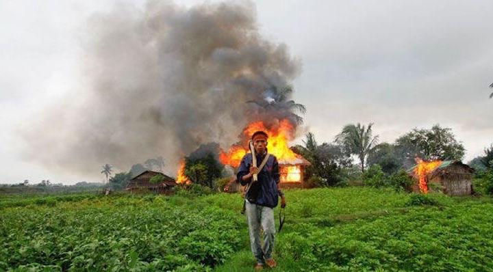 Un-homme-armé-quitte-village-enflammé