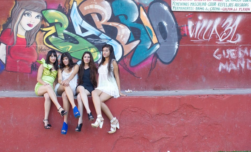Quatre élèves de Guido Models devant un graffiti portant le nom du quartier. Crédits : Prudence Alba pour Guido Models Facebook Officiel.